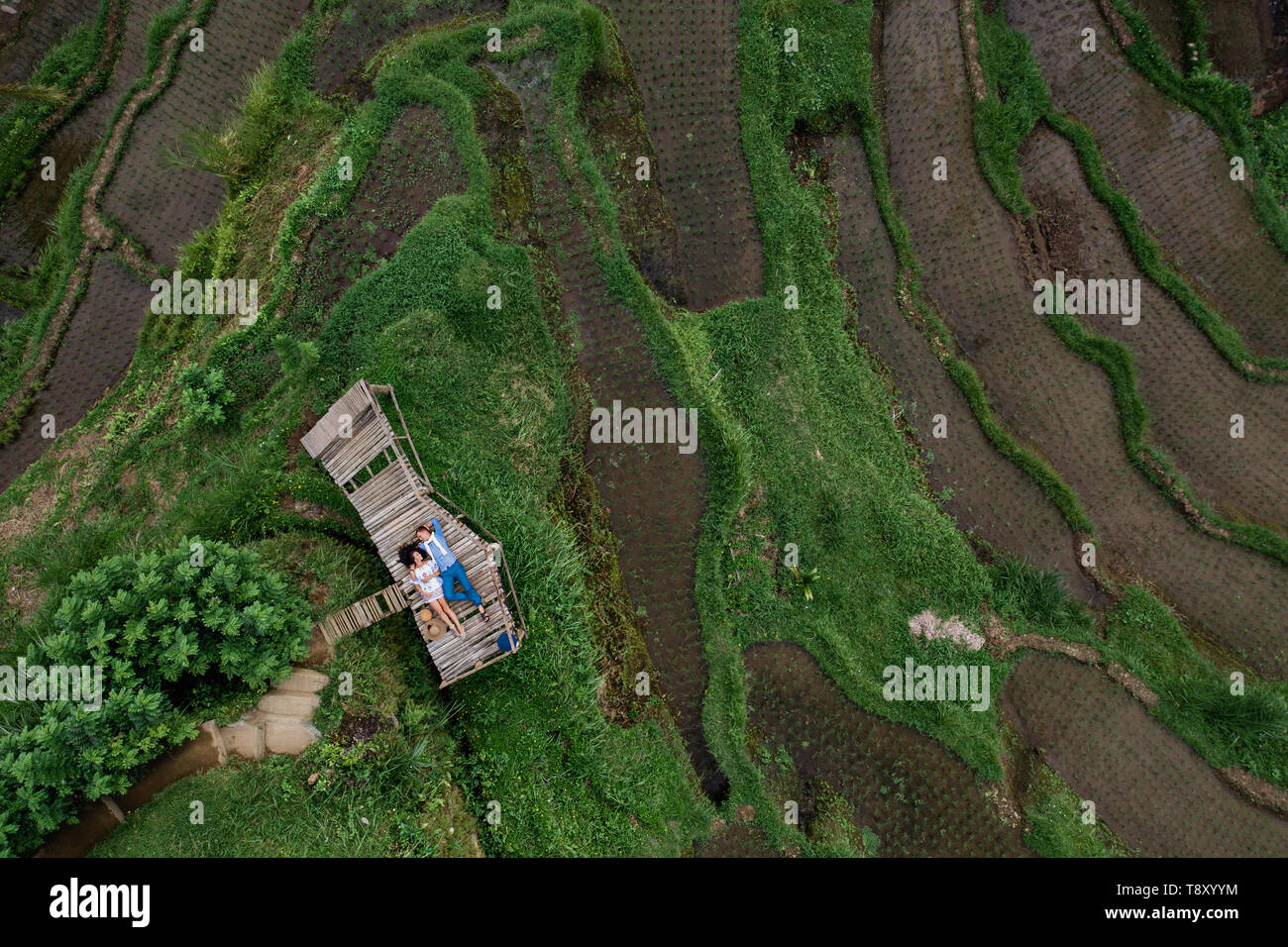 Aerial view on top. Two lovers of young people lie on a wooden bridge. Happy couple traveling at Bali, rice terraces of Tegalalang, Ubud. Honeymoon - Stock Image