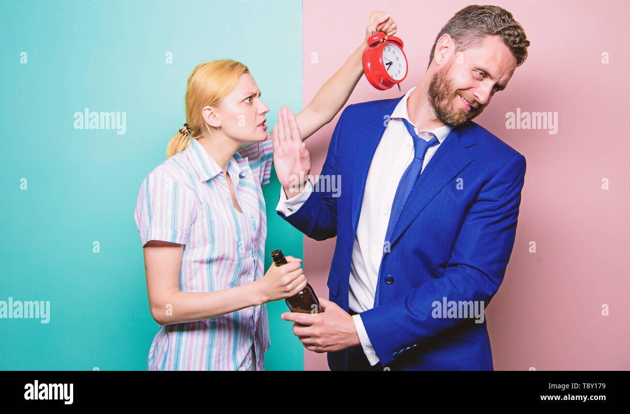 After corporate party. Man suffering from alcoholism. Angry wife meeting drunk husband late at home. Businessman with alcohol bottle and woman with alarm clock. Addictive alcoholism or alcohol abuse. - Stock Image