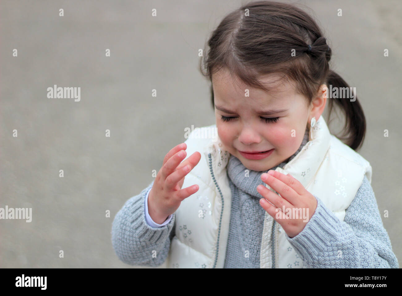 crying girl with pigtails in a sweater and vest raises her hands up - Stock Image