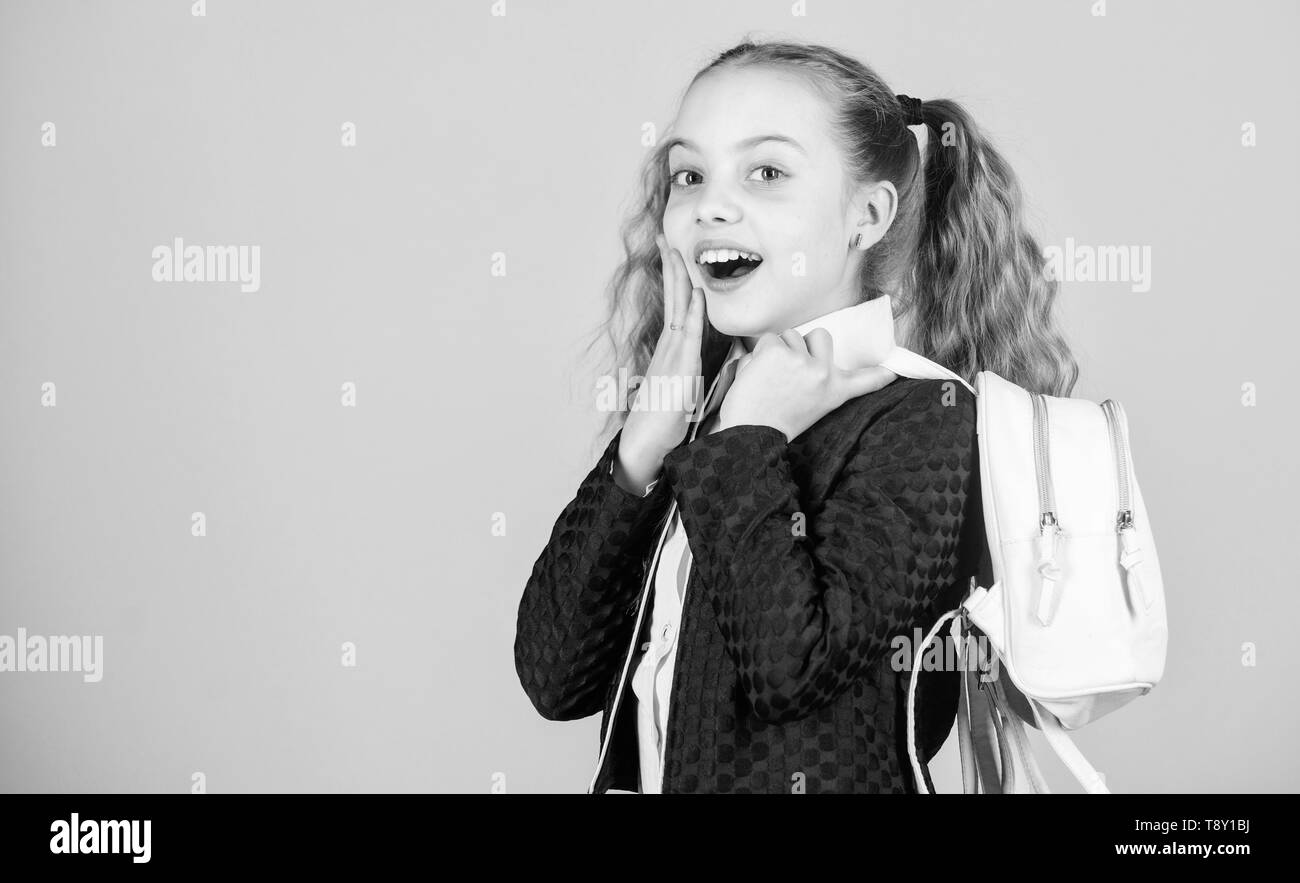 Girl little fashionable cutie carry backpack. Popular useful fashion accessory. Schoolgirl ponytails hairstyle with small backpack. Carrying things in backpack. Learn how fit backpack correctly. - Stock Image