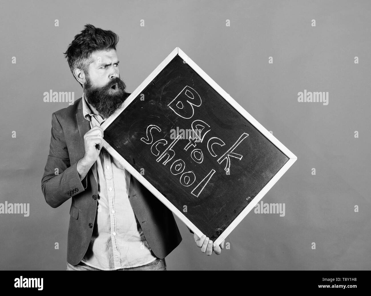 Teaching stressful occupation. Take it easy. Teacher with tousled hair stressful about school year beginning. Teacher bearded man holds blackboard with inscription back to school red background. - Stock Image