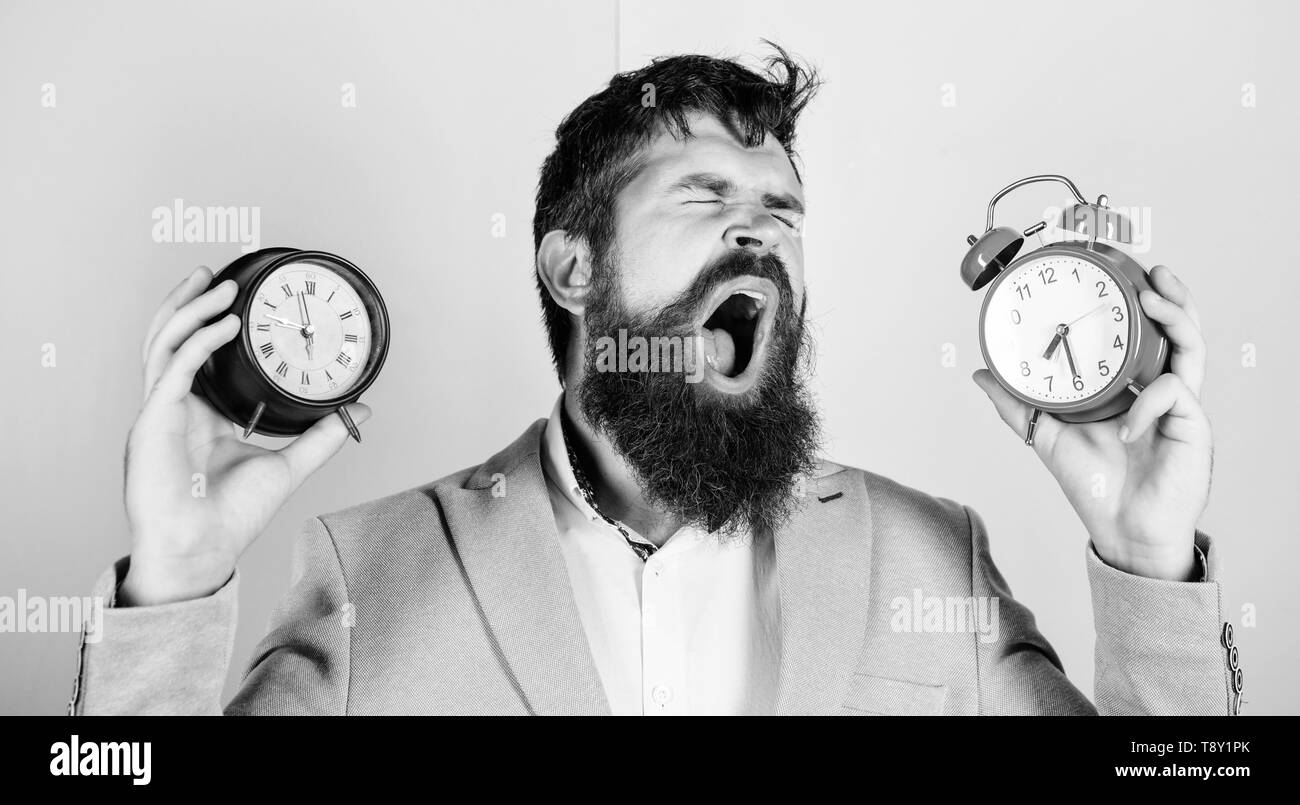 Guy unshaven puzzled face having problems with changing time. Time zone. Changing time zones affect health. Does changing clock mess with your health. Man bearded hipster hold two different clocks. - Stock Image