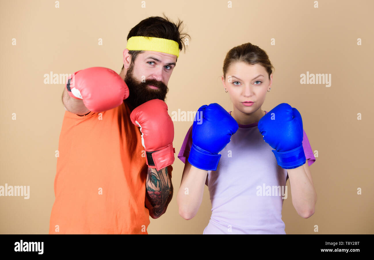training with coach. sportswear. Fight. knockout and energy. couple training in boxing gloves. punching, sport Success. Happy woman and bearded man workout in gym. Hustle, hit and never quit. - Stock Image