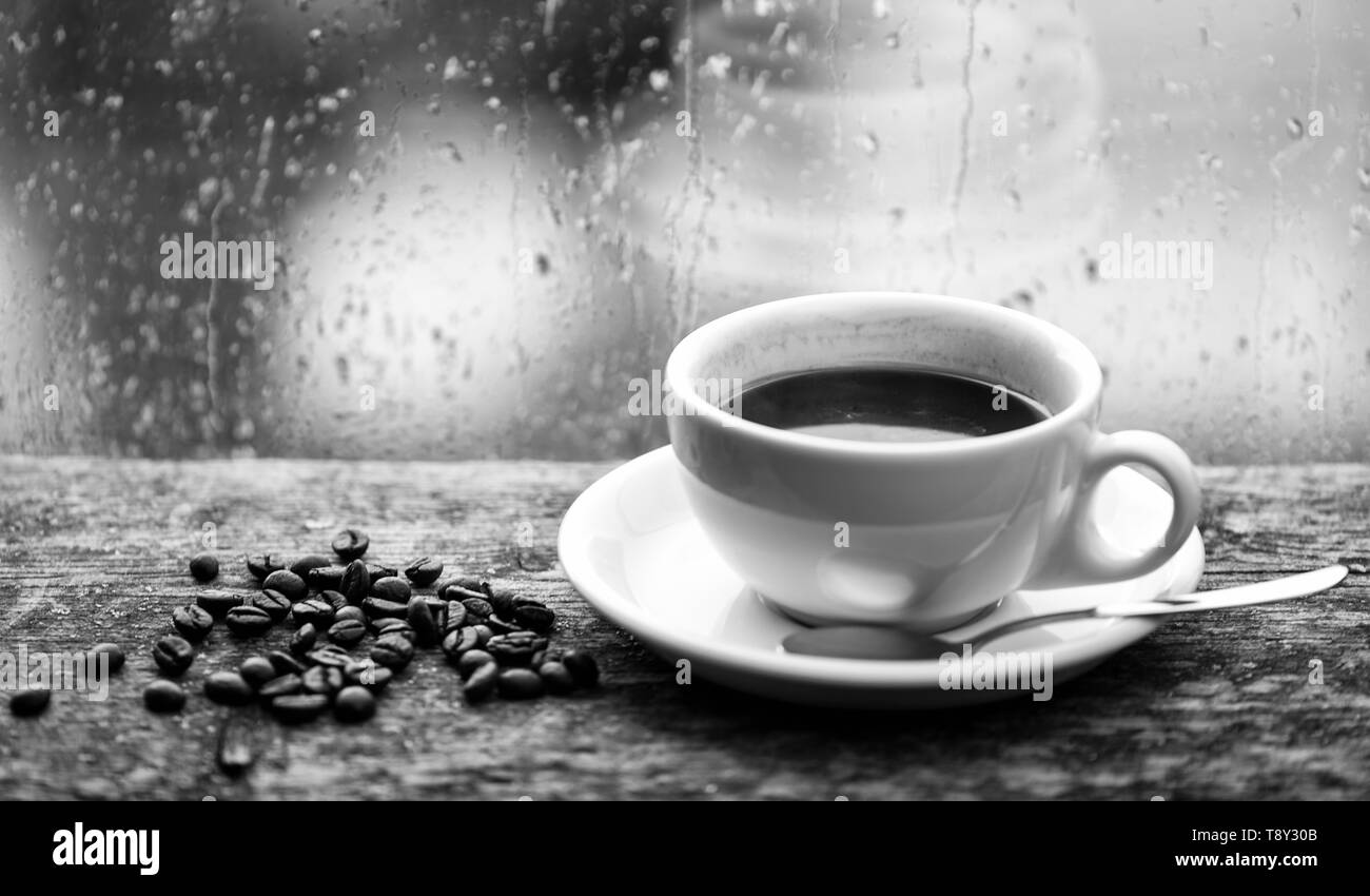 Autumn cloudy weather better with caffeine drink. Enjoying coffee on rainy day. Coffee morning ritual. Fresh brewed coffee white mug and beans on windowsill. Wet glass window and cup of hot coffee. - Stock Image