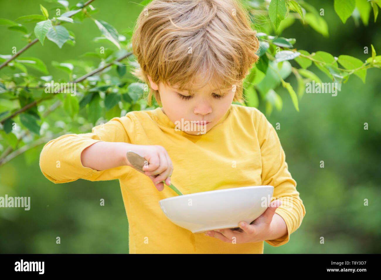 Son And Eating Milk Porridge Cereal For Breakfast Good Morning Small Boy Eating Outdoor Child Development Little Boy Eat Healthy Food Childhood Happiness Healthy Food And Dieting Family Day Stock Photo