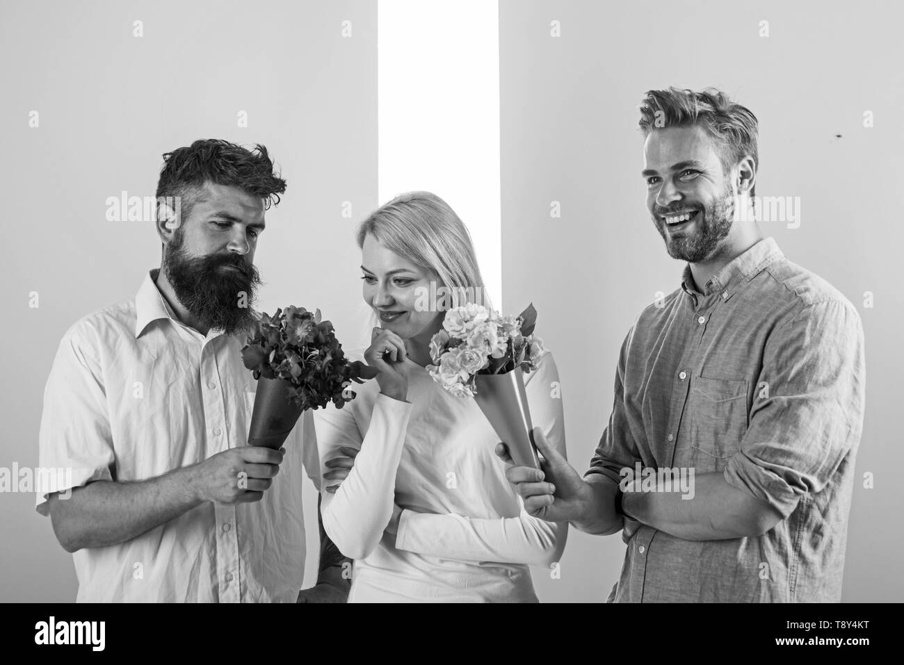 Men competitors with bouquets flowers try conquer girl. Girl likes to be in middle attention. Love triangle. Woman thoughtful has opportunity choose partner. Girl popular receive lot men attention. - Stock Image