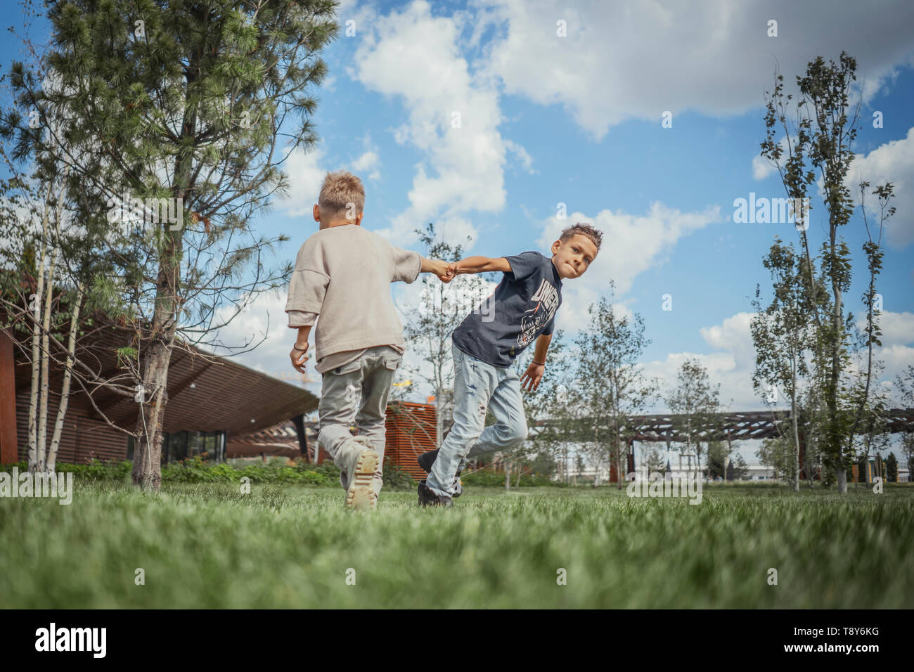 Two brothers turning around, whirling and having fun at green park. Happy family concept. - Stock Image