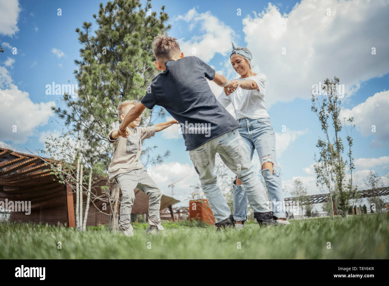 Young mum turning around, whirling and having fun with her sons at green modern park. Happy family concept. - Stock Image