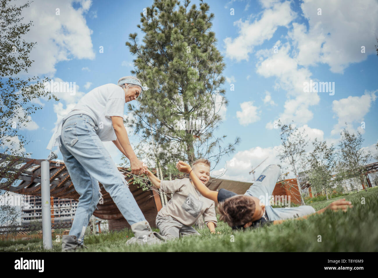 Young blonde mum turning around, whirling with her sons at park. Happy family concept. Family is on foreground and focus, park is blurred. - Stock Image