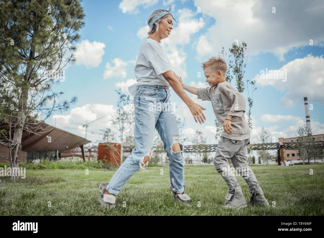 Young mum turning around, whirling with her son at park. Happy family concept. - Stock Image