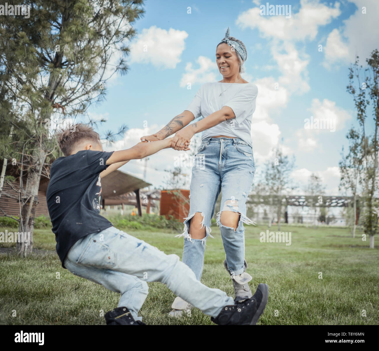 Pretty mum turning around, whirling with her son at park. Happy family concept. - Stock Image