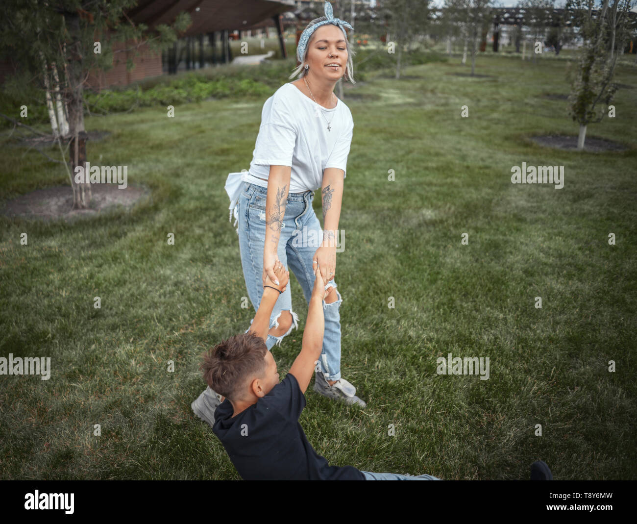 Young pretty mum whirling with her son at park. Happy family concept. - Stock Image