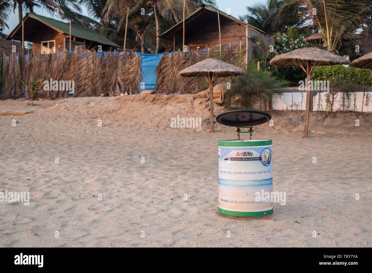 Garbage bins for trash on Agonda Beach in Goa, India, at sunset. - Stock Image