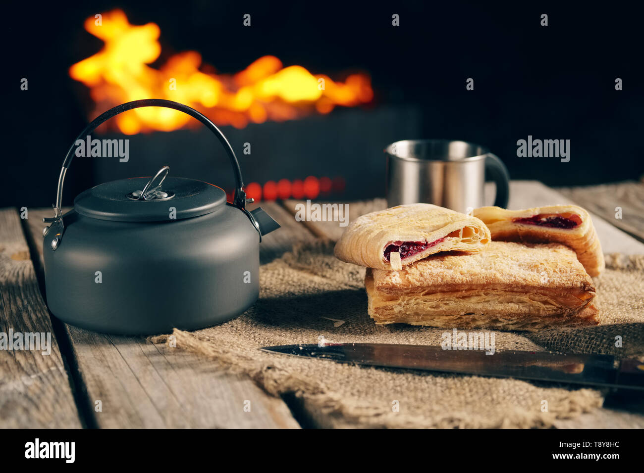 Late snack for two at night outdoor kamping - biscuit and tea near fireplace. - Stock Image