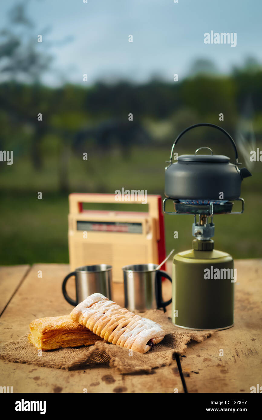 Making coffee or tea on portable gas stove on the nature. Travel, adventure, camping gear, outdoors items. - Stock Image