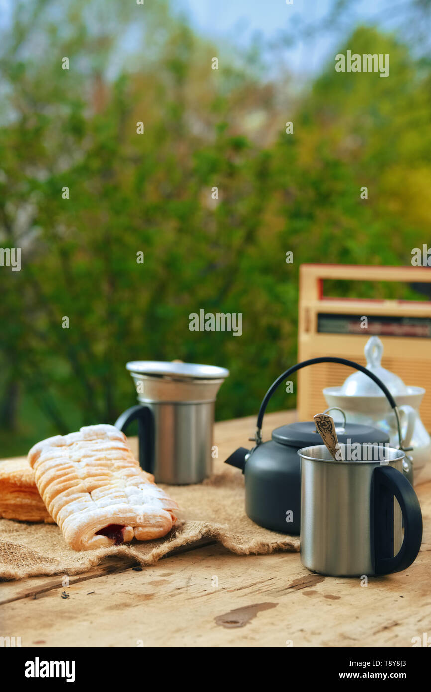 Camping kettle with a mug and biscuit  on the table outdoors . Snack in summer evening. - Stock Image