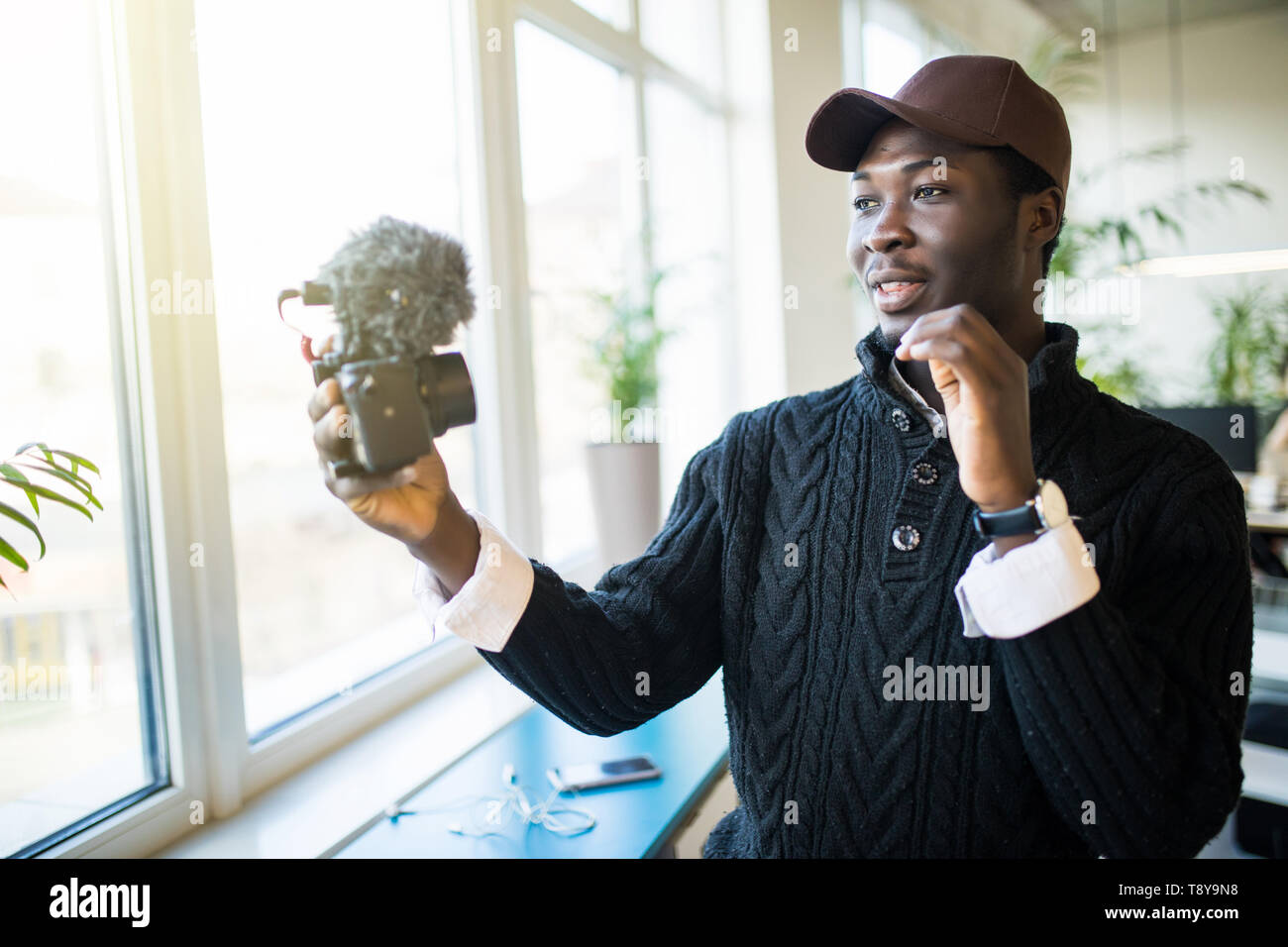 Young african man speaker talking on digital camera recording vlog. African male vlogger or business trainer speaking shooting blog filming reportage  Stock Photo