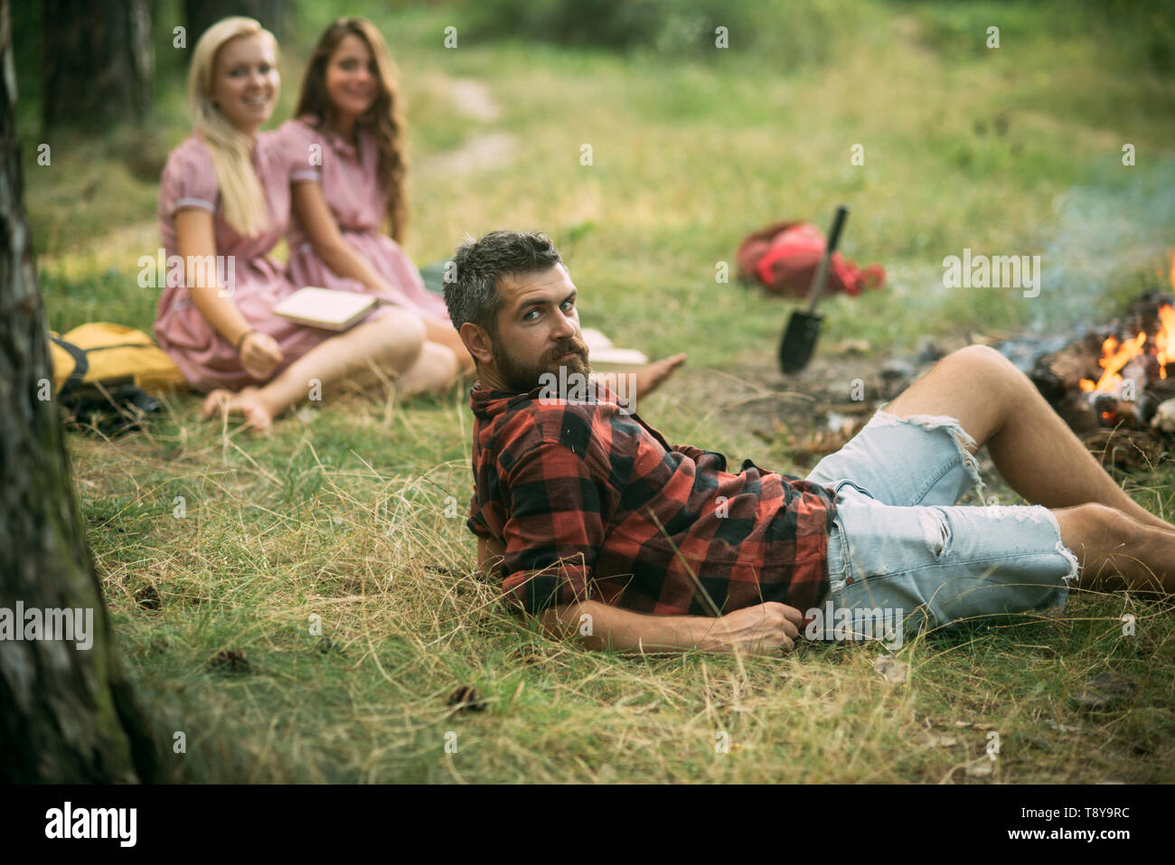 Bearded man in lumberjack shirt lying on grass, unity with nature concept. Group of young hikers camping in forest - Stock Image