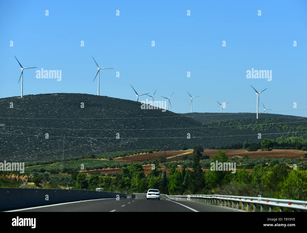 Road on mountain landscape. Asphalt road and wind turbines on blue sky. Direction and destination. Alternative energy sources. Summer vacation - Stock Image