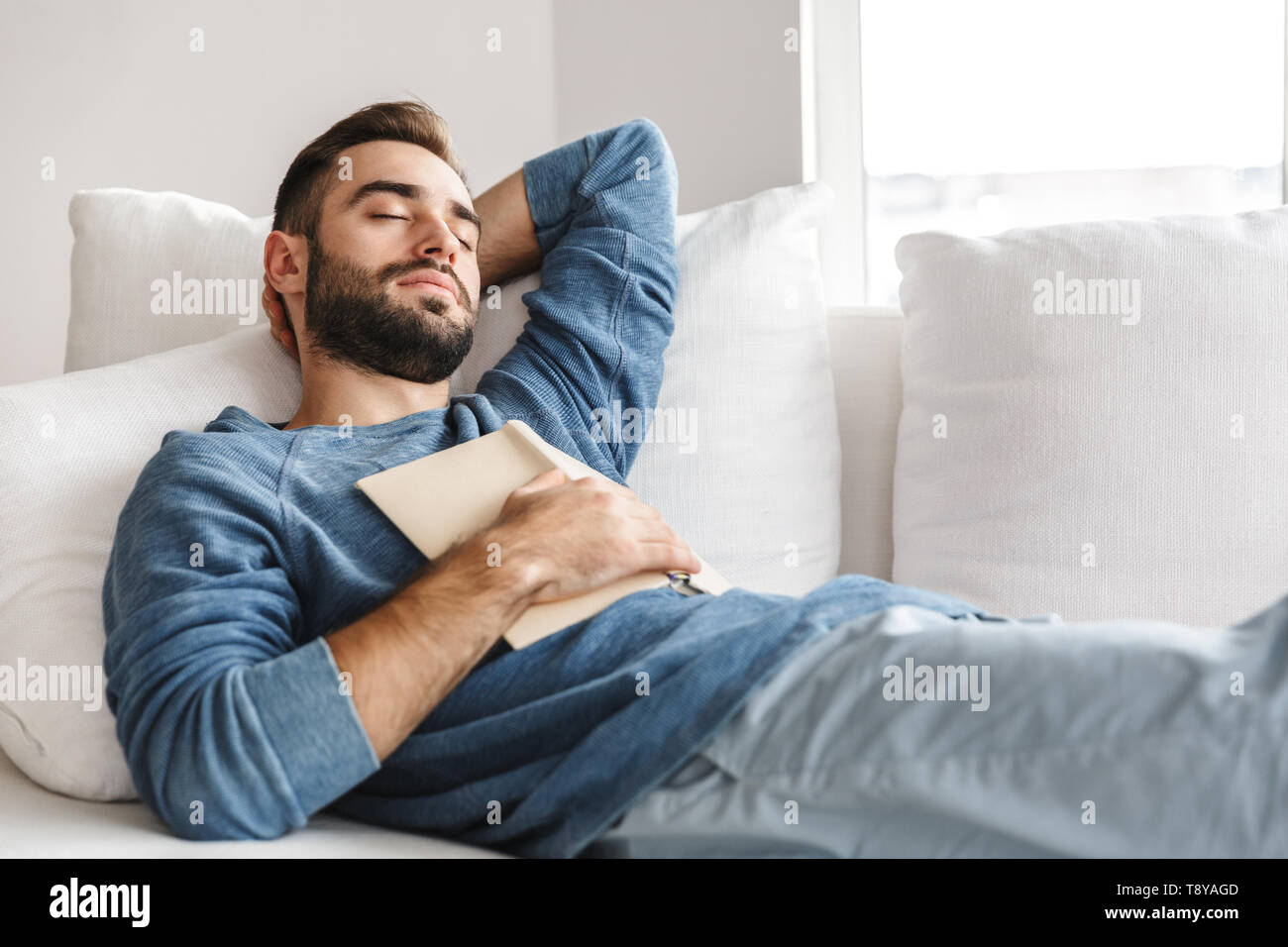 Attractive young man relaxing on a couch at home, sleeping - Stock Image