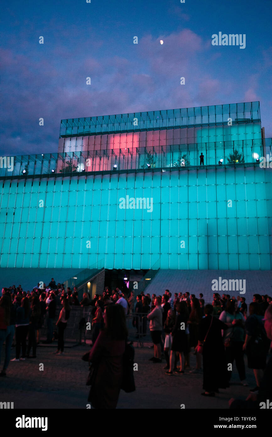 Festival event party concert with people standing on a square in a city center at night. Backlit glass construction above them Stock Photo