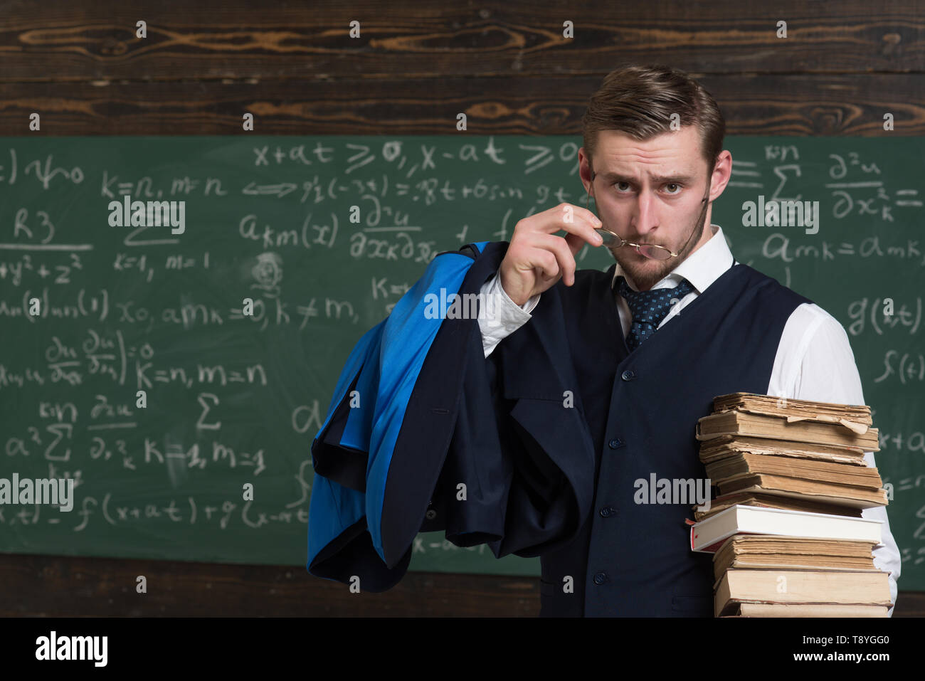 Are you serious Teacher formal wear and glasses looks suspicious, chalkboard background. Chalkboard full of math formulas. Man in end of lesson - Stock Image