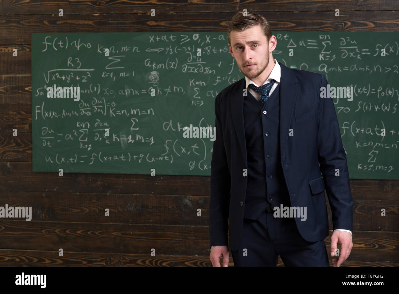 Talented mathematician. Man formal wear classic suit looks smart, chalkboard with equations background. Genius solved mathematics problem. Teacher - Stock Image