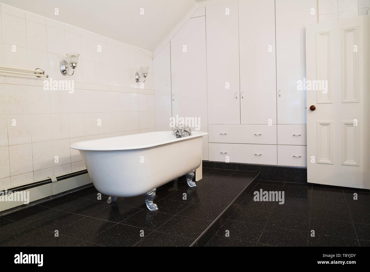 White antique cast iron claw foot bathtub on elevated black granite tile platform in main bathroom with white cabinets and drawers on upstairs floor i - Stock Image