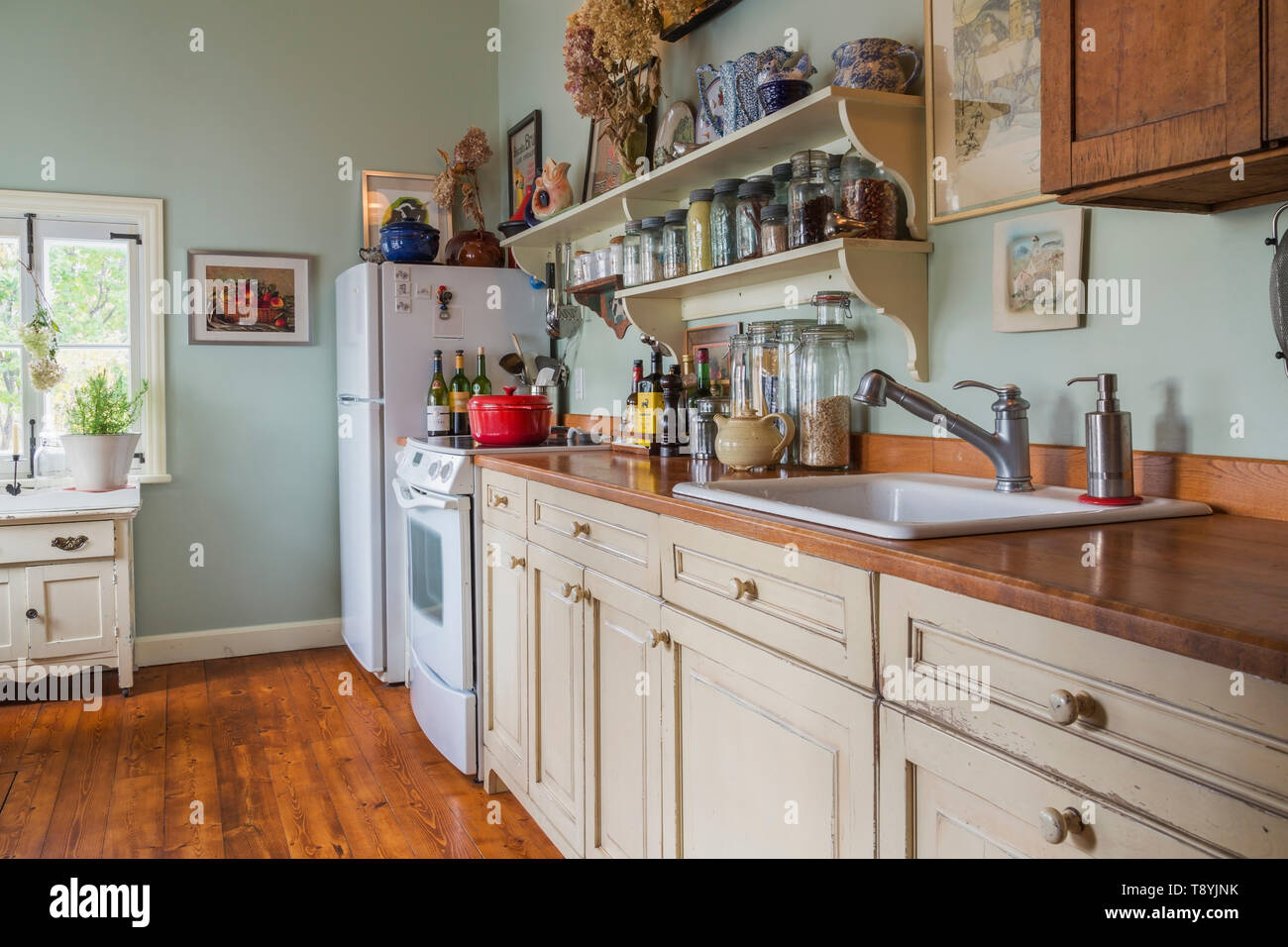 View of country style kitchen with old herbs and spice glass jars on countertop, shelves and pinewood floorboards inside an old renovated 1650s house, Quebec, Canada. This image is property released. CUPR0336 Stock Photo