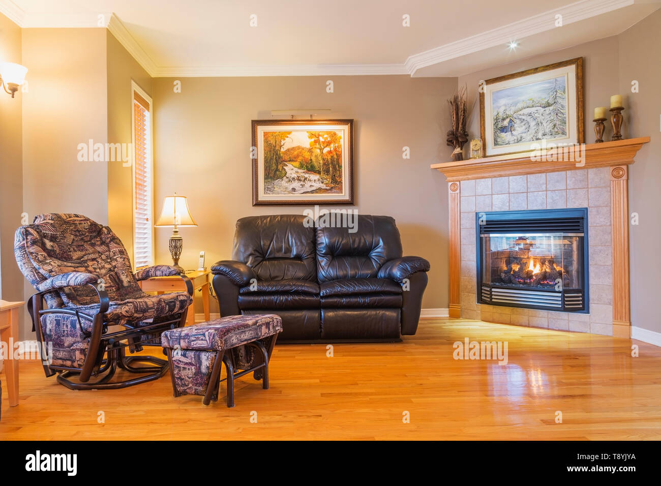 Black leather sofa and reclining armchair in living room with gas fireplace and oakwood floorboards inside a country cottage style house, Quebec, Canada. This image is property released. CUPR0340 Stock Photo