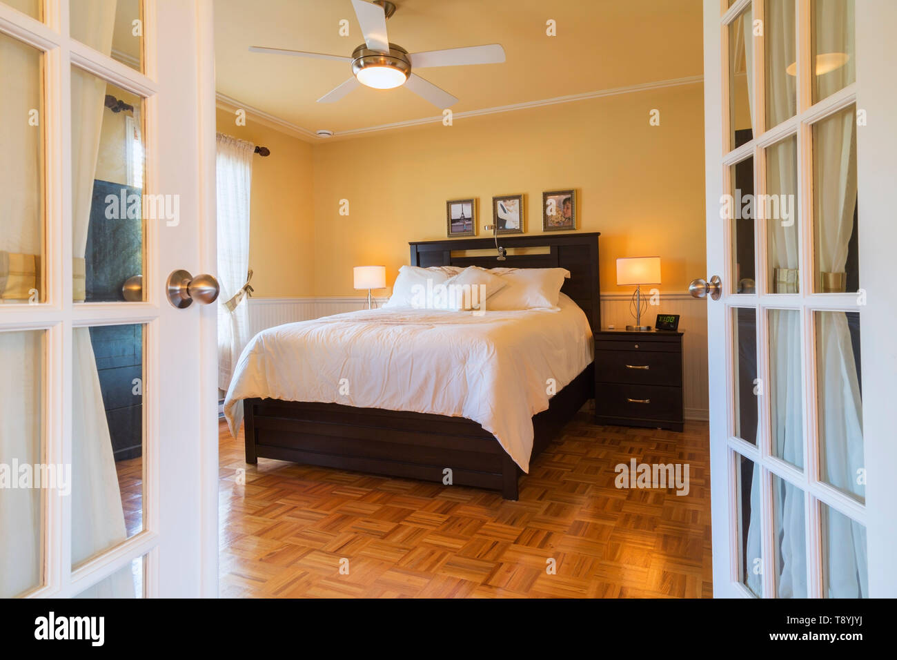 Queen-size bed with wooden headboard, end table and opened ...