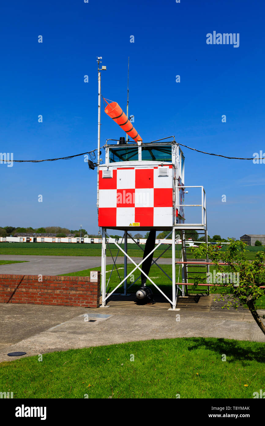 Control tower and windsock at the former RAF Breighton airfield in the East Riding of Yorkshire. Home to the Lincoln Aero Club and the Real Aeroplane  - Stock Image