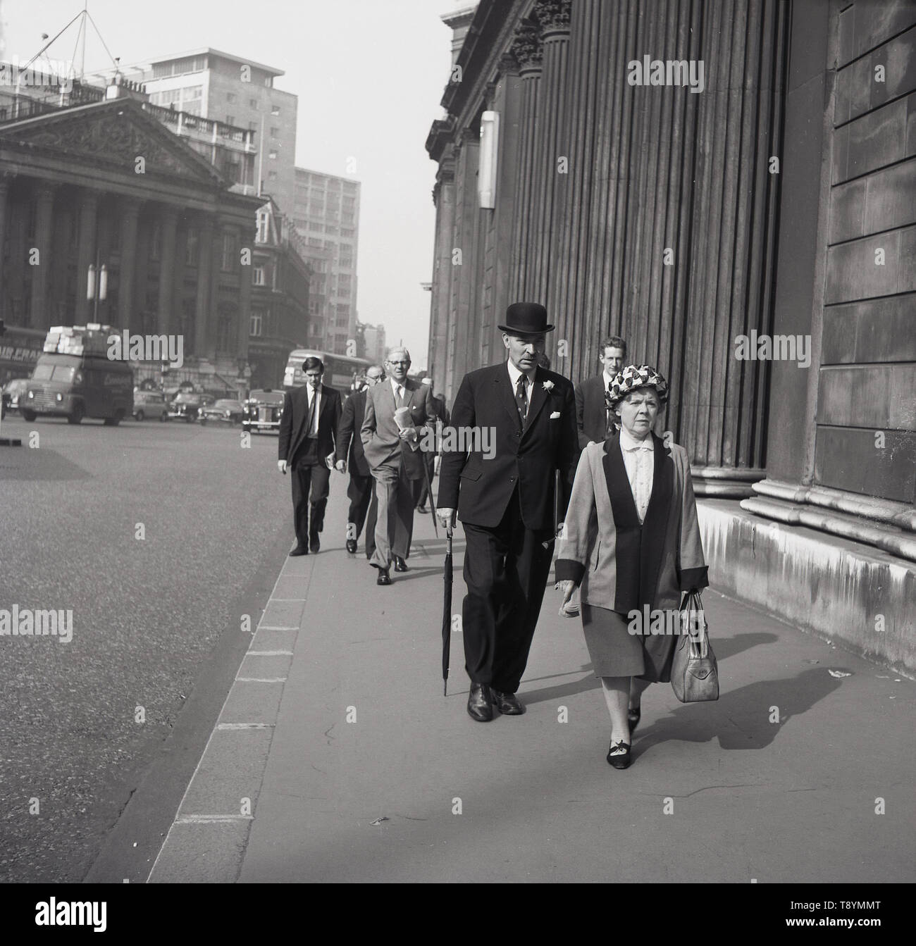 1950s, historical, city of London, people, incluing a suited city gentleman wearing a top hat and carrying an umbrella walking past the Bank of England. - Stock Image