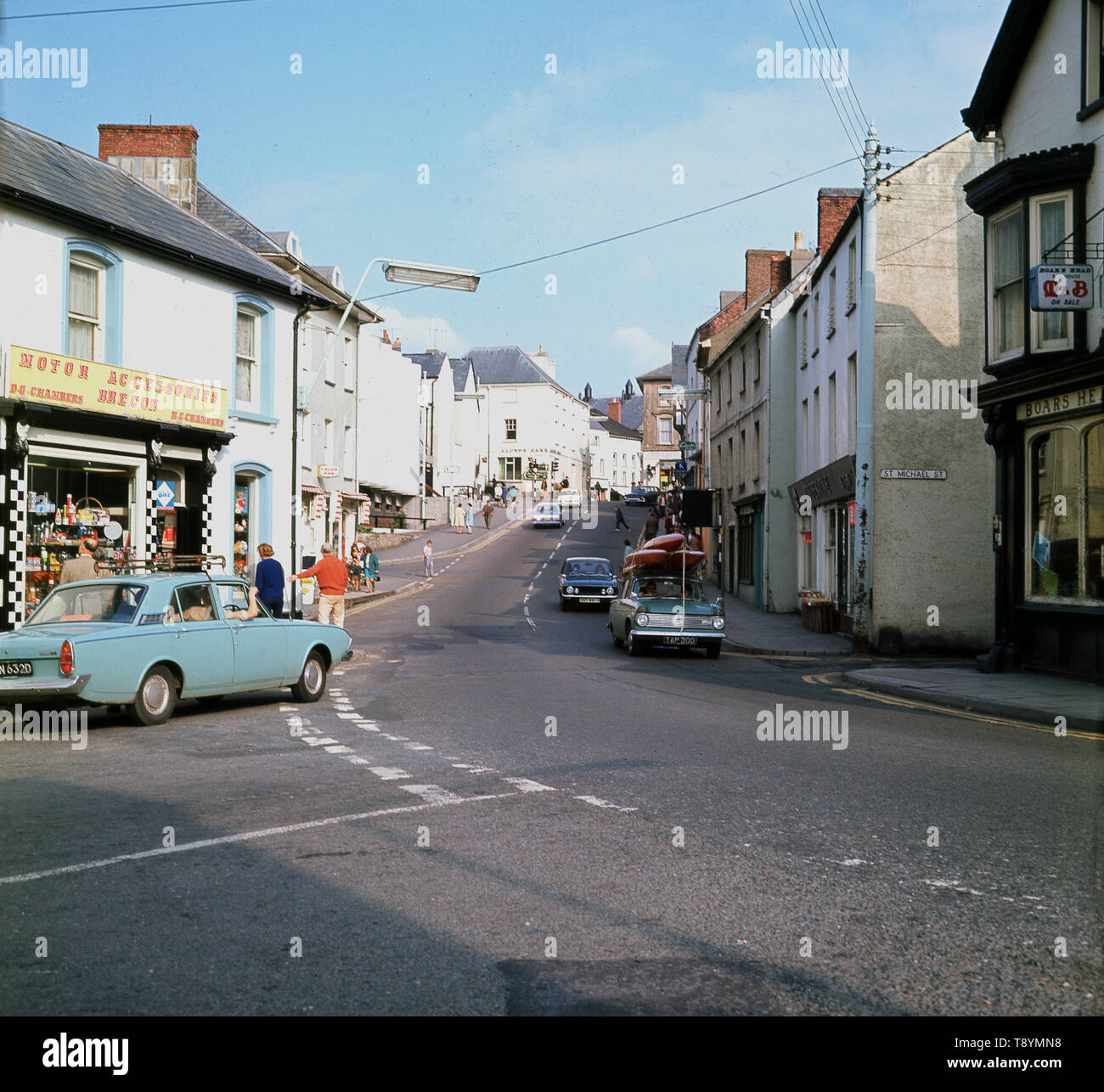 1960s, historical picture from this era of St Michael street, Brecon, Powys, Wales, showing the Chambers family Motor Parts shop and on the far right, the  M & B Boars Head pub. - Stock Image