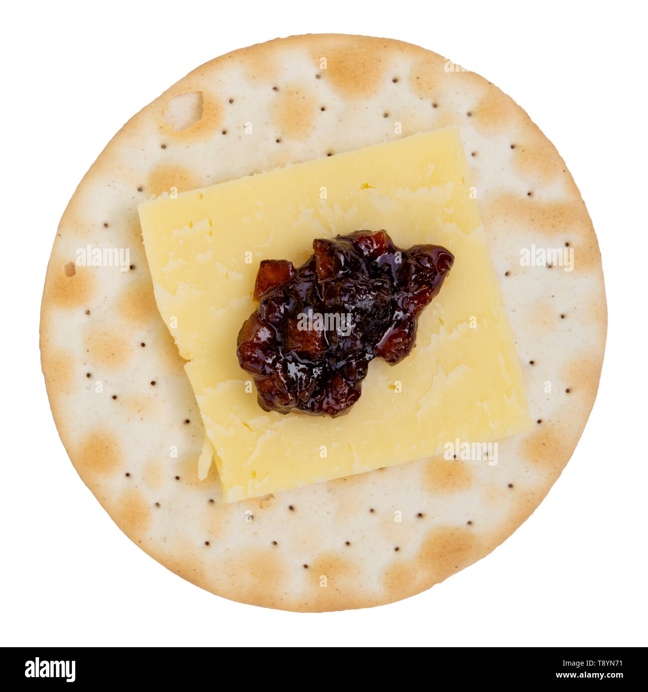 Cheddar cheese & pickle on a round cracker or biscuit, UK. Carrs table water biscuit shot from above and cut out or isolated on a white background. - Stock Image