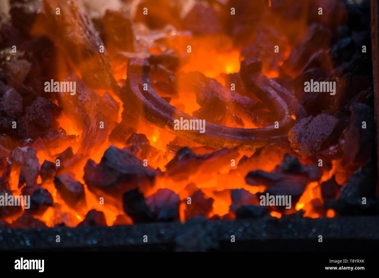blacksmith furnace with burning coals, tools, and glowing hot horseshoe, close-up - Stock Image