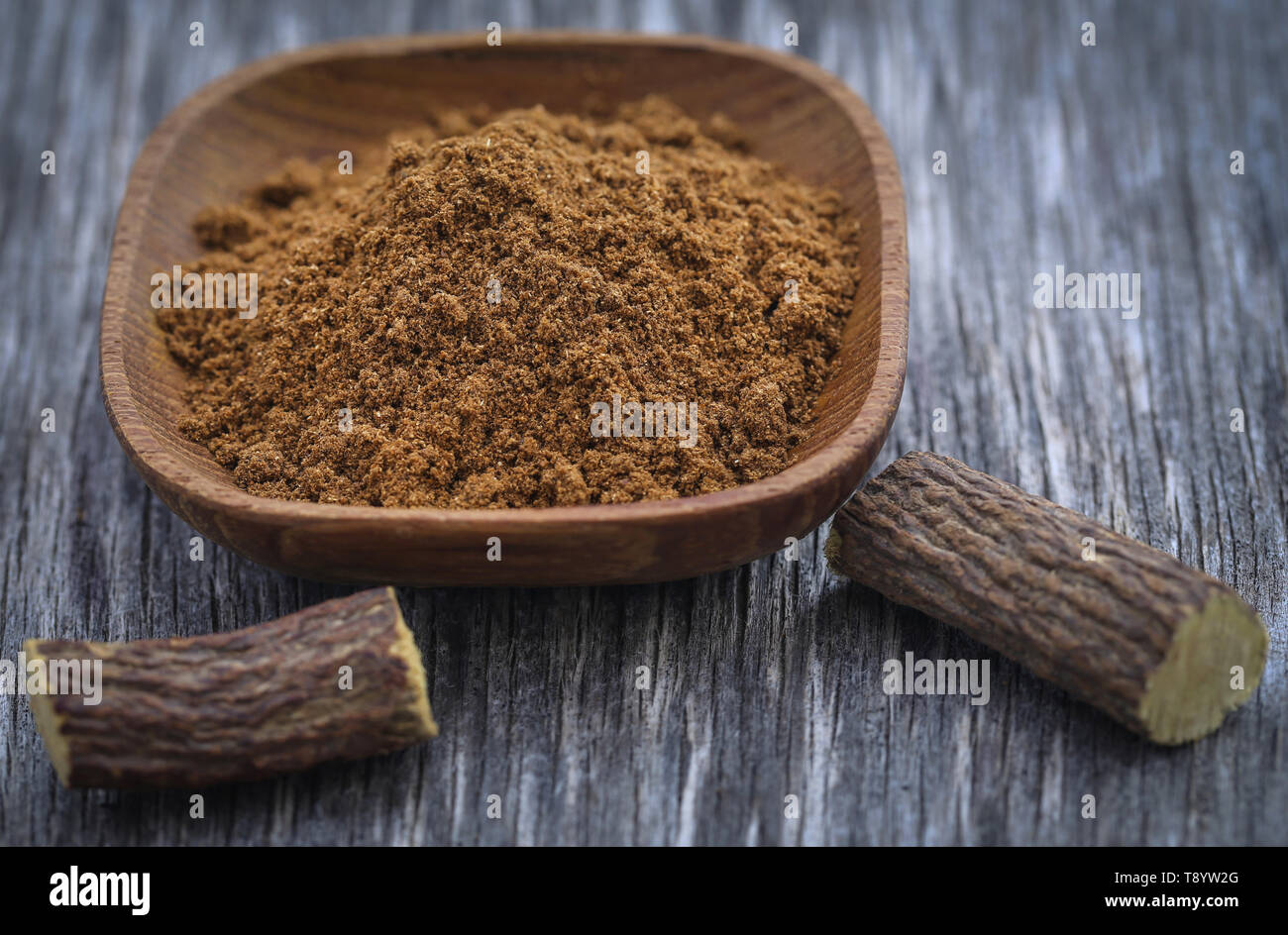 Liquorice stick and ground herbs in wooden bowl on textured surface - Stock Image