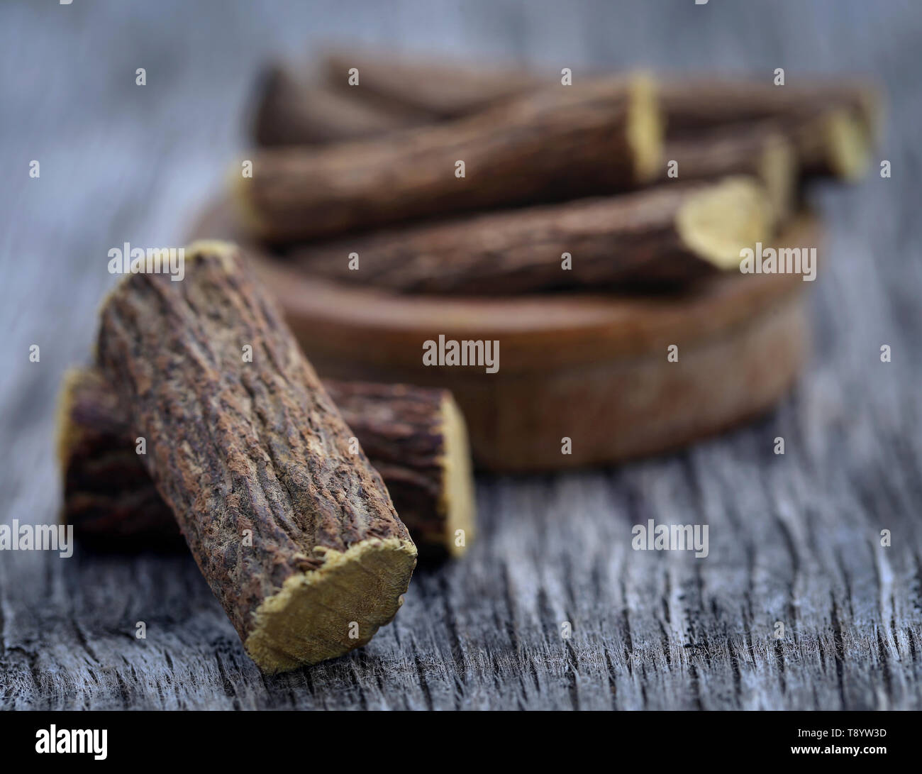 Liquorice stick in wooden bowl on textured surface - Stock Image