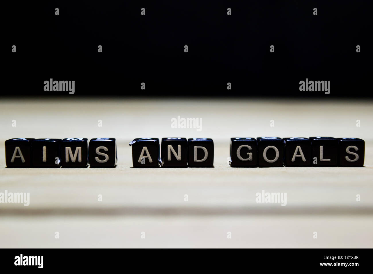 Aims and Goals concept wooden blocks on the table. With personal development and motivation concept on blurred or black background Stock Photo