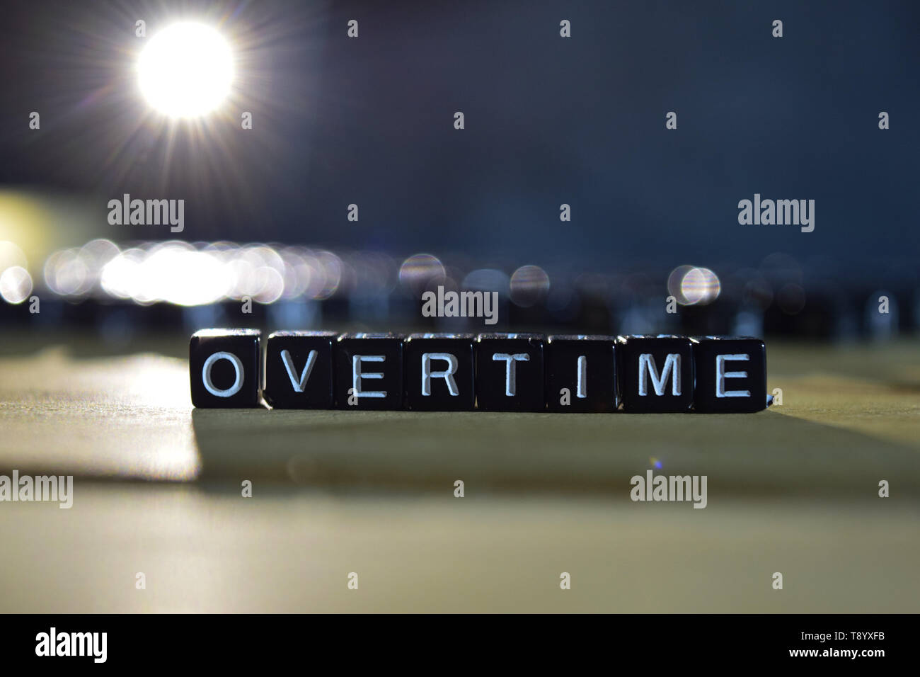 OVERTIME concept wooden blocks on the table. With personal development and motivation concept on blurred or black background - Stock Image