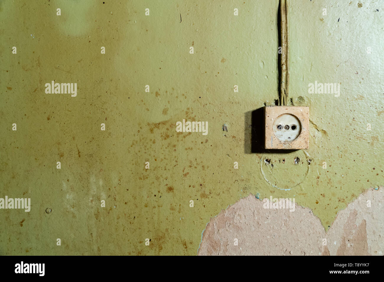 Old power socket isolated on damaged green wall - reconstruction background - Stock Image