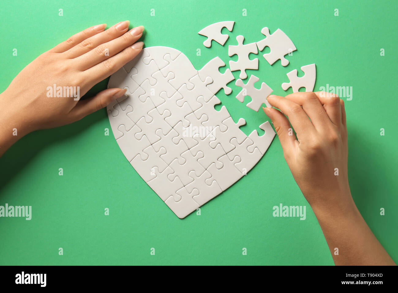 Woman doing jigsaw puzzle on color background Stock Photo