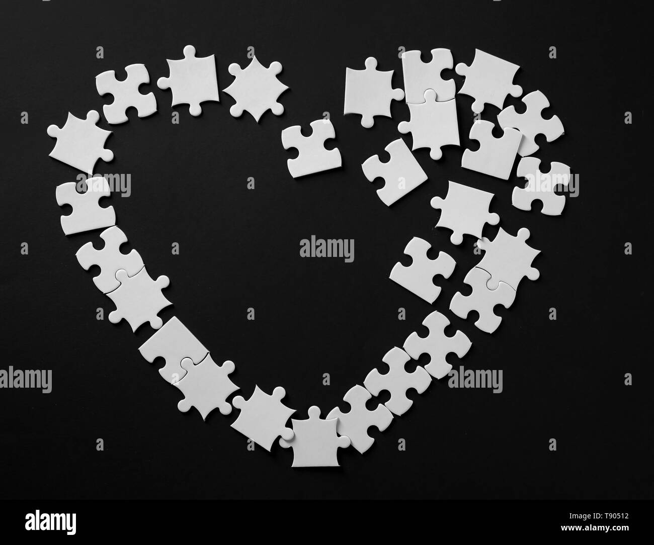 Heart made of jigsaw puzzle pieces on dark background - Stock Image