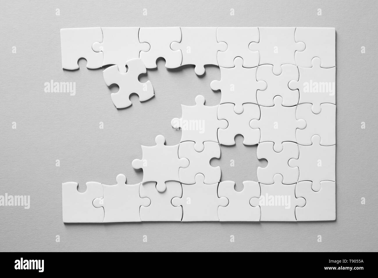Incomplete jigsaw puzzle on light background - Stock Image