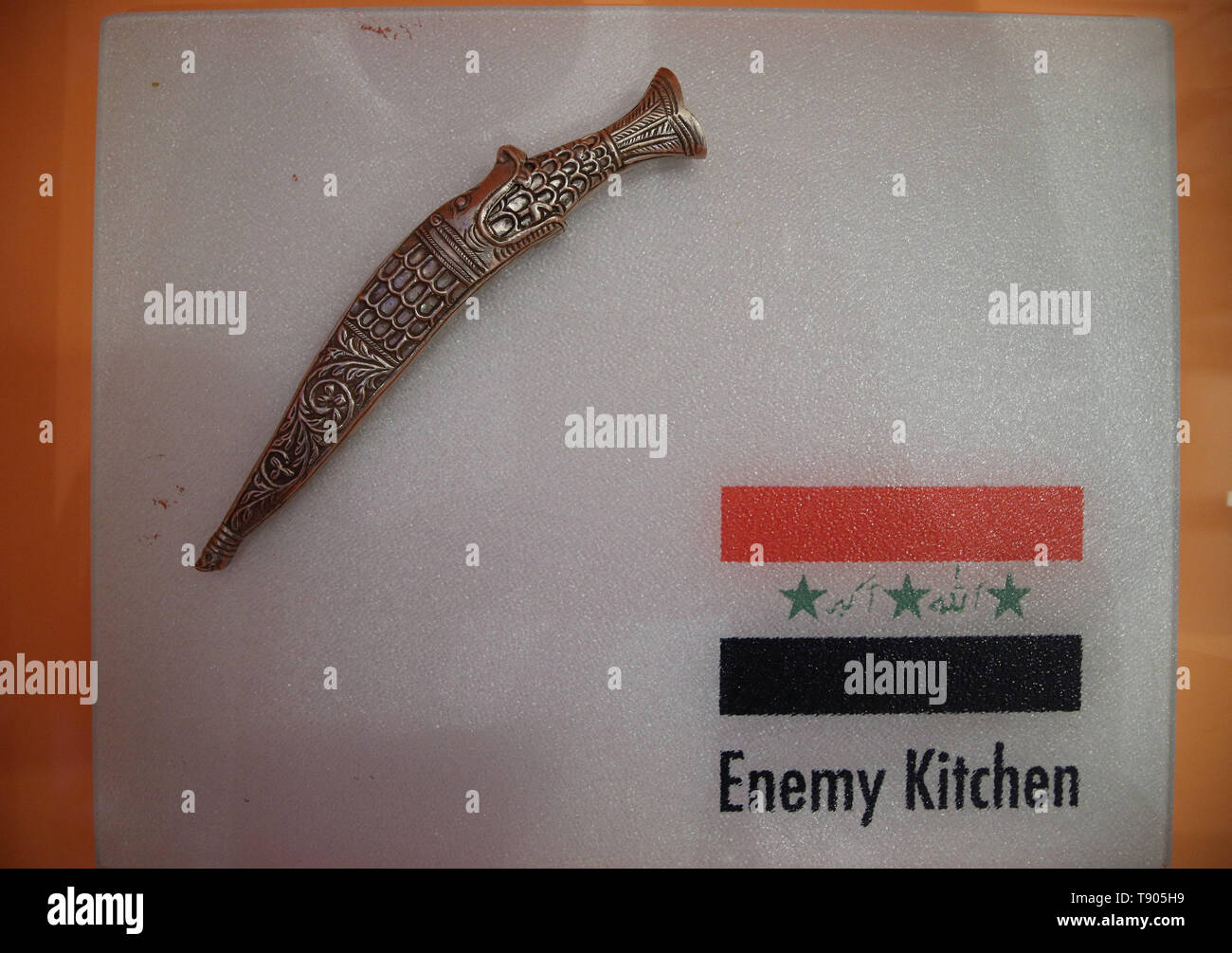 A knife (made especially for the project by Saddam Hussein's sword-maker) resting on a cutting board, as part of 'Enemy Kitchen' - a project by artist Michael Rakowitz, an Iraqi Jew, that opens up conversations about the relationship between two warring countries - on display at the FOOD: Bigger than the Plate exhibition at the Victoria and Albert Museum in London. - Stock Image