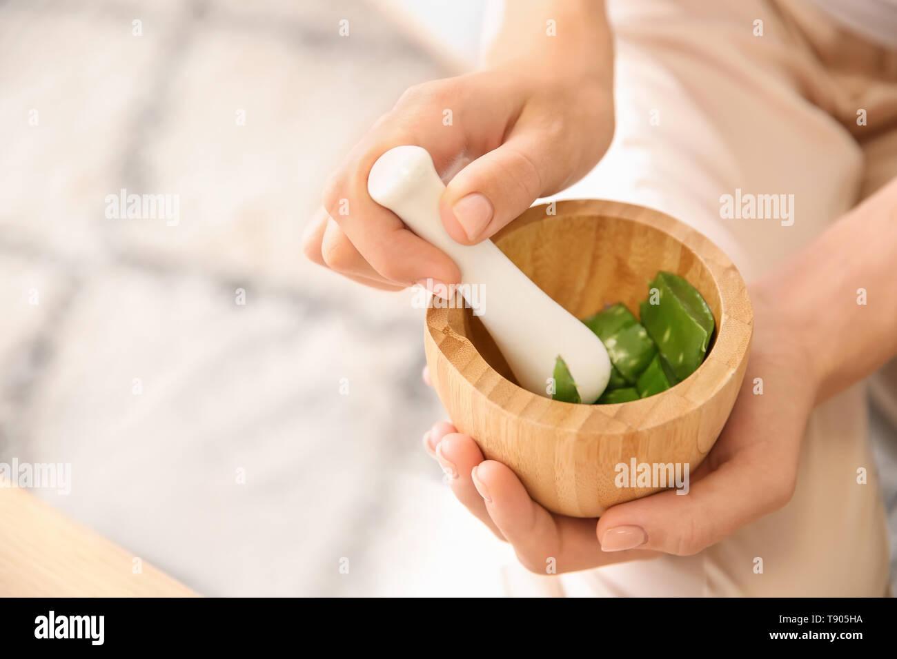 Young woman making healthy facial mask with aloe vera extract at home, closeup - Stock Image