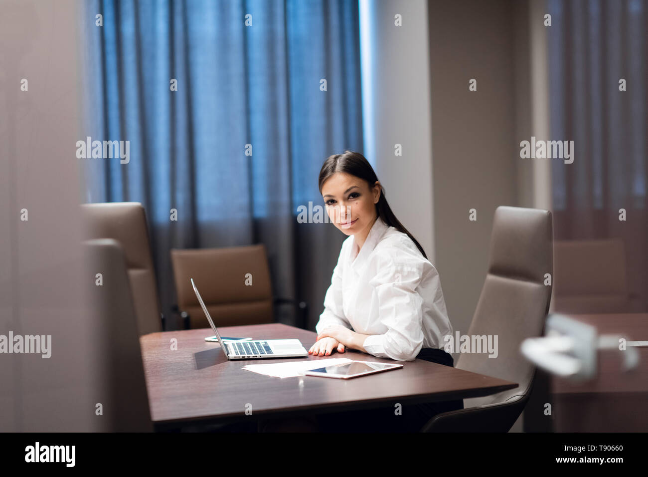 Beautiful young businesswoman using laptop in conference room Stock Photo