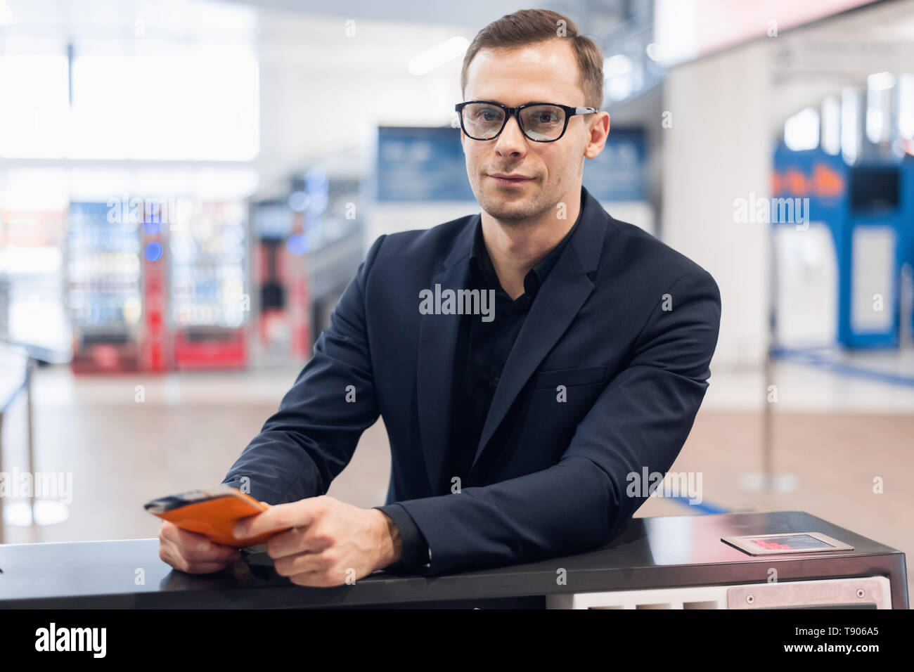 Midsection Of Male Passenger Showing Passport At Airport - Stock Image