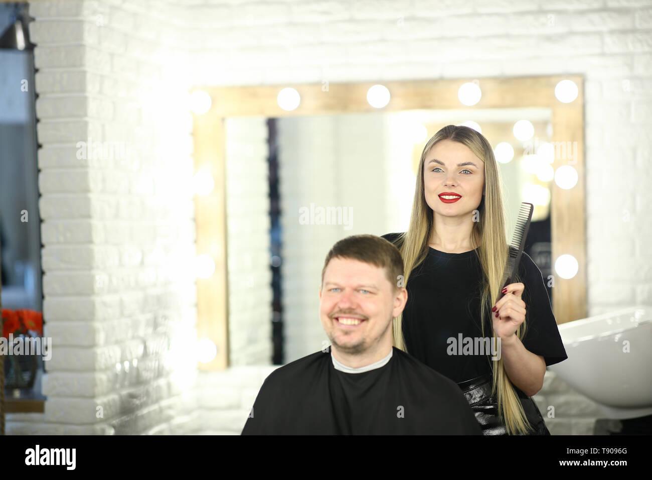 Girl Hairstylist and Man Customer in Beauty Studio Stock Photo