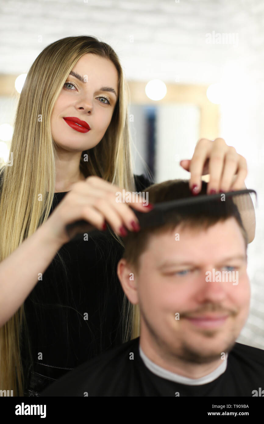 Woman Hairstylist Combing Client with Hairbrush - Stock Image